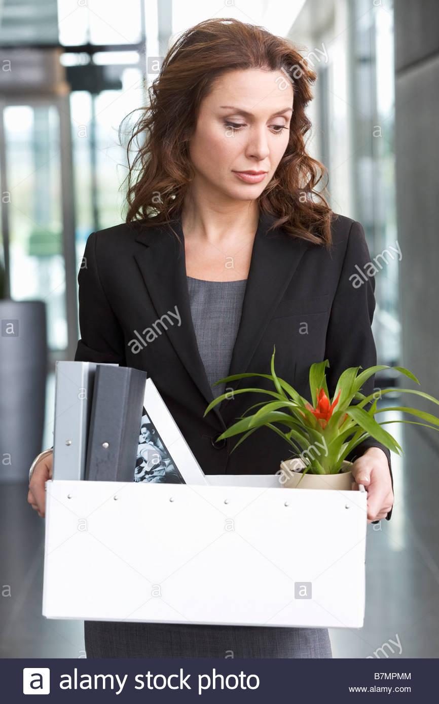 Una imprenditrice ridondante tenendo i suoi averi home Immagini Stock