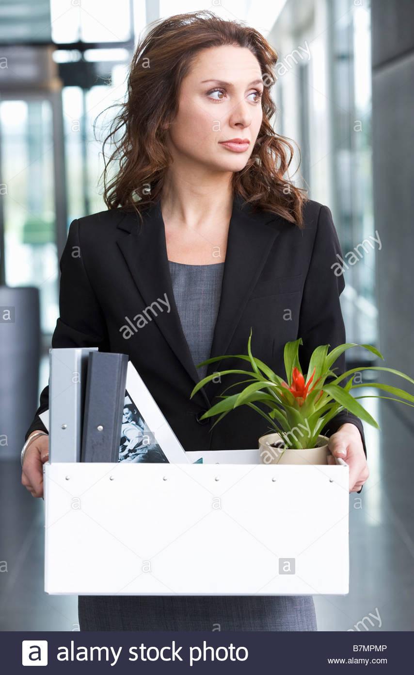 Una imprenditrice ridondante tenendo i suoi averi home in una scatola Immagini Stock