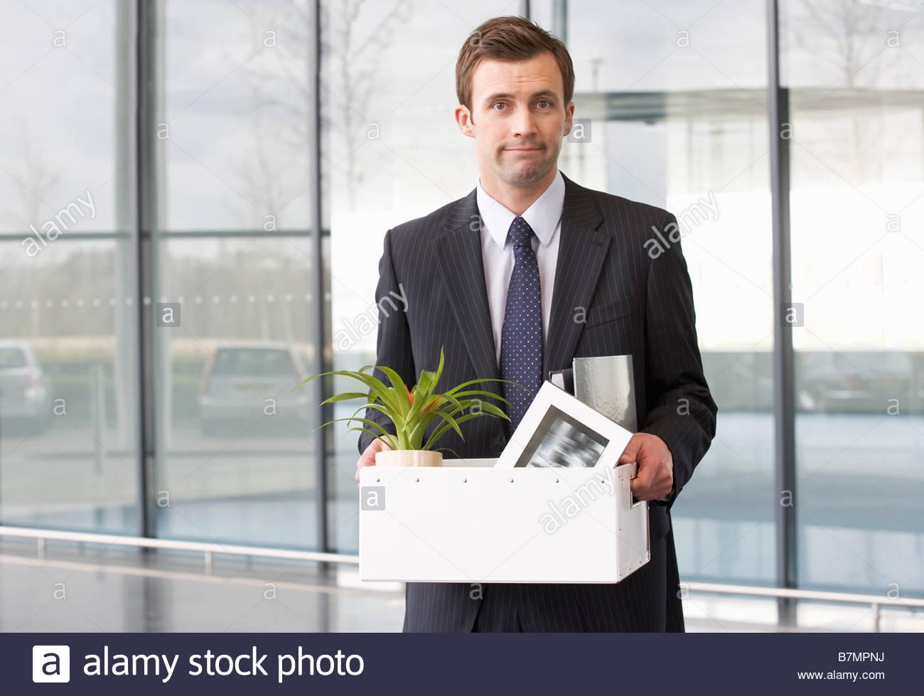 Un imprenditore ridondante tenendo le sue cose a casa in una scatola Immagini Stock