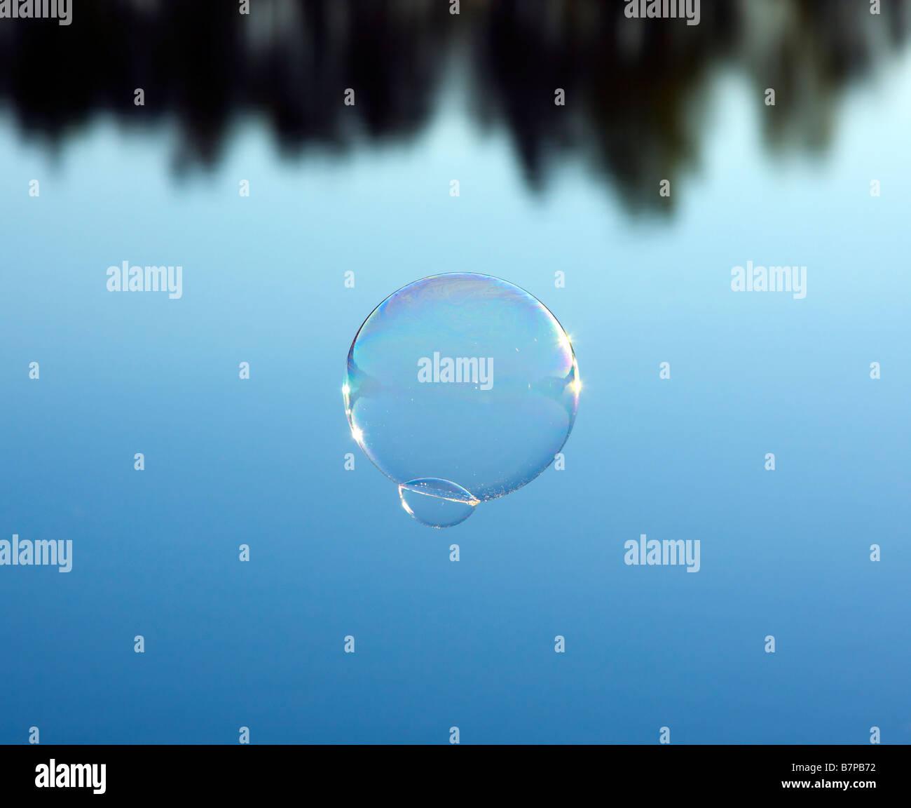 Bubble vola sopra l'acqua blu Immagini Stock