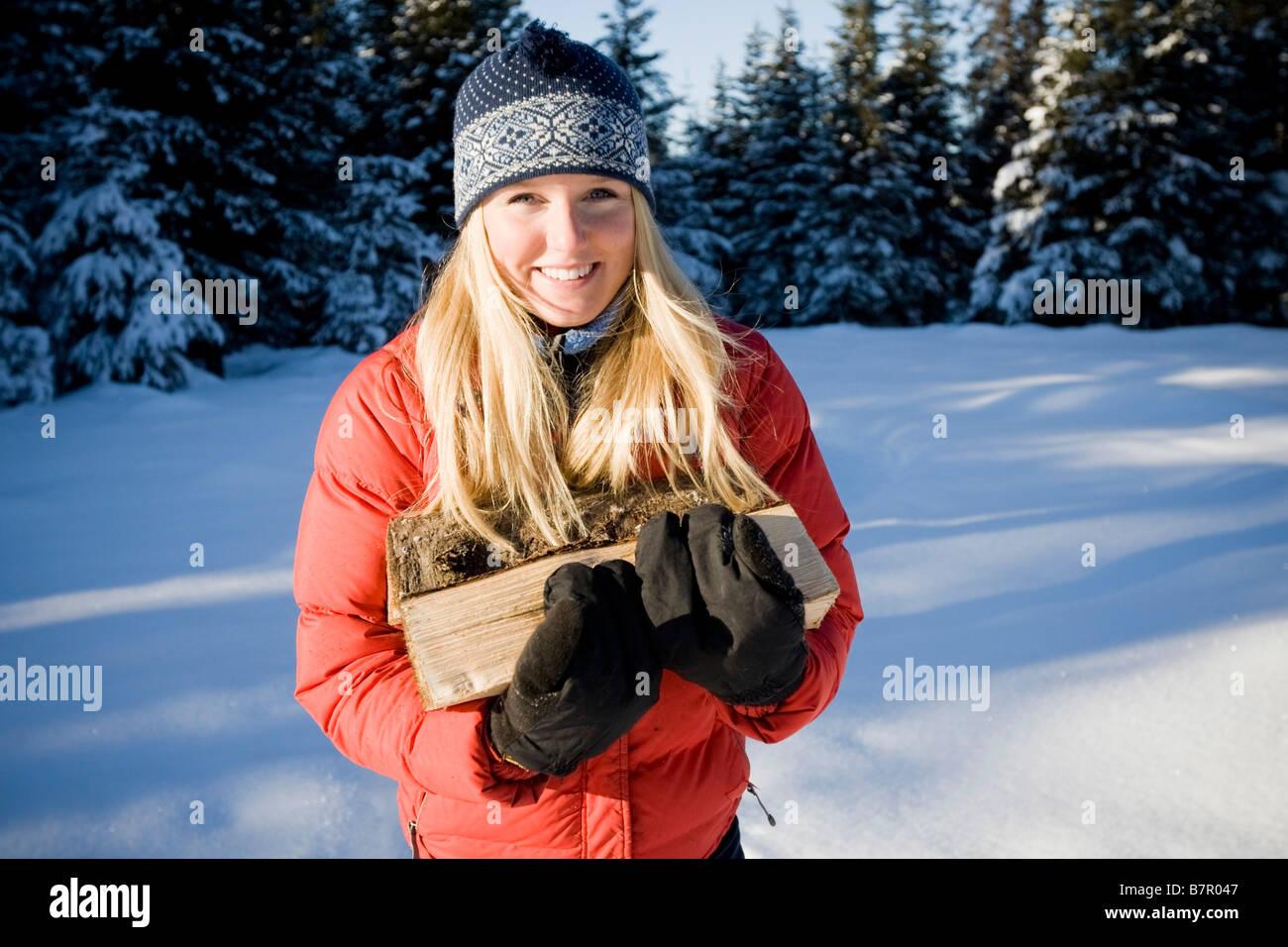 Giovane donna con le racchette da neve porta un trito di legno vicino a Omero, Alaska durante l'inverno. Immagini Stock