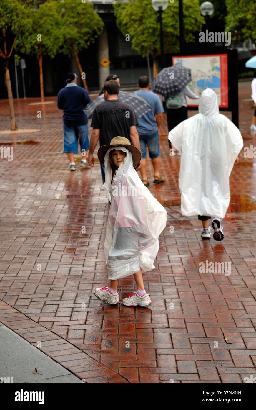 Bambino (6 anni) indossa Episteme bush-hat rispetto alla plastica impermeabile. Darling Harbour, Sydney, Australia Immagini Stock