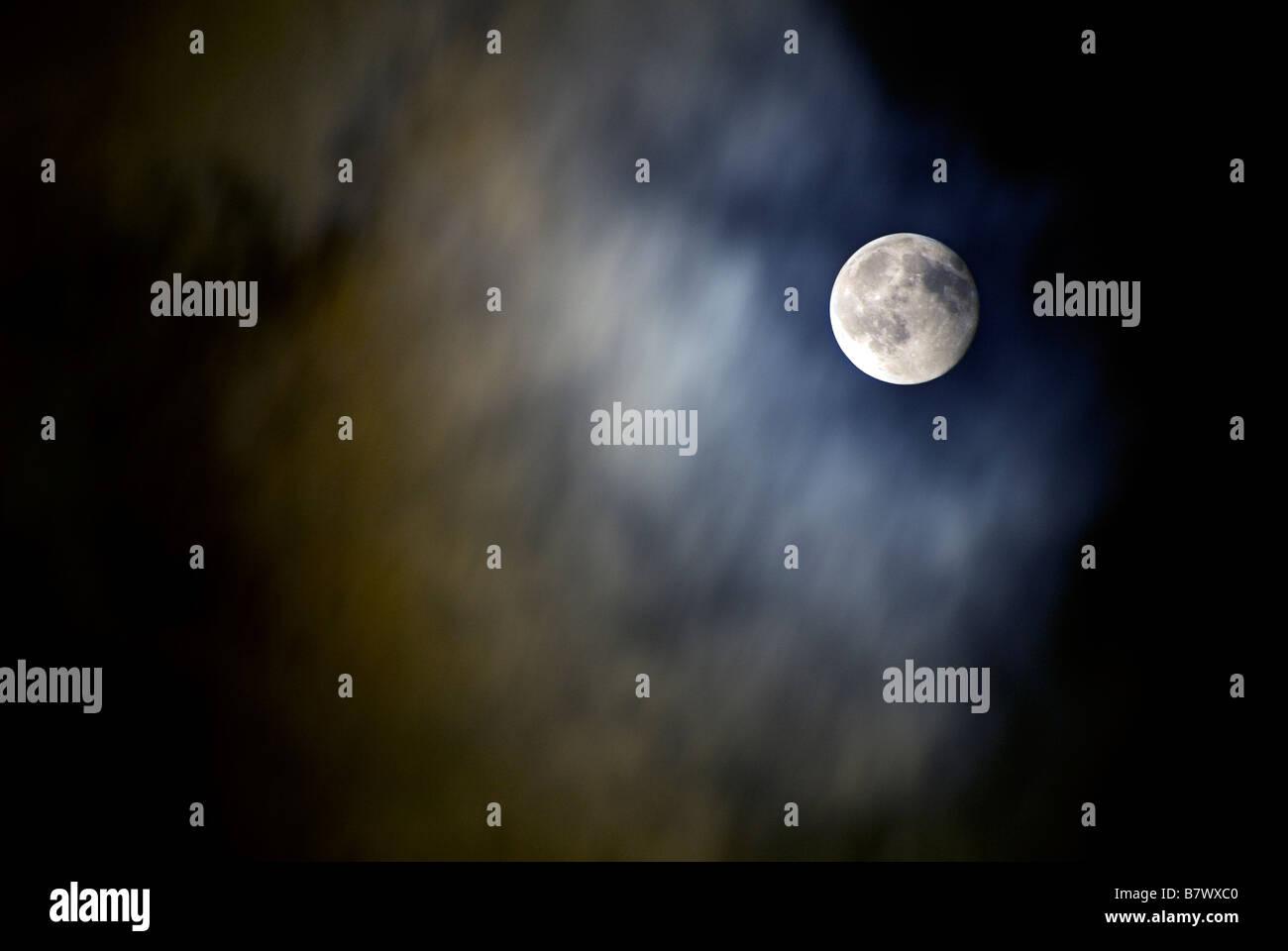 Luna SHOT IN UN nuvoloso cielo notturno Immagini Stock