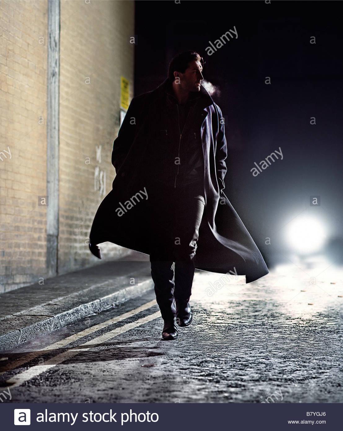 Uomo in soprabito correndo giù per strada di notte - Luci auto dietro Immagini Stock