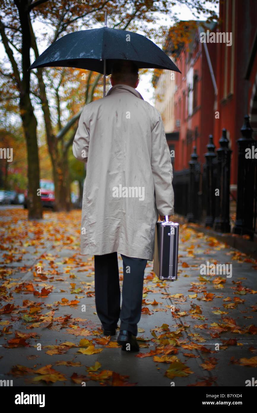 Imprenditore a camminare sulla strada sotto ombrellone Immagini Stock