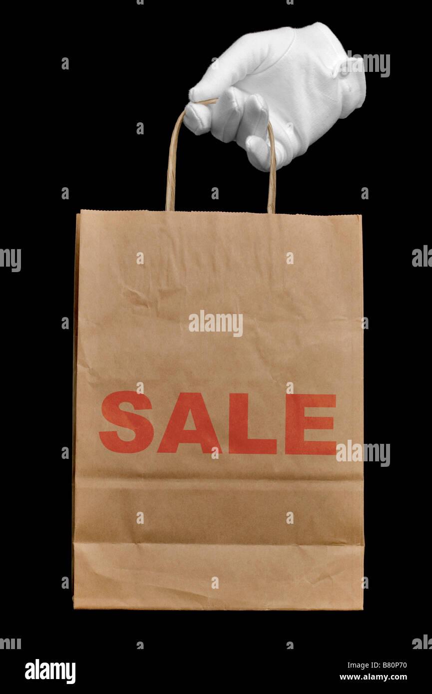 La mano in un guanto bianco in possesso di una carta riciclata marrone shopping bag con la parola vendita scritto Immagini Stock