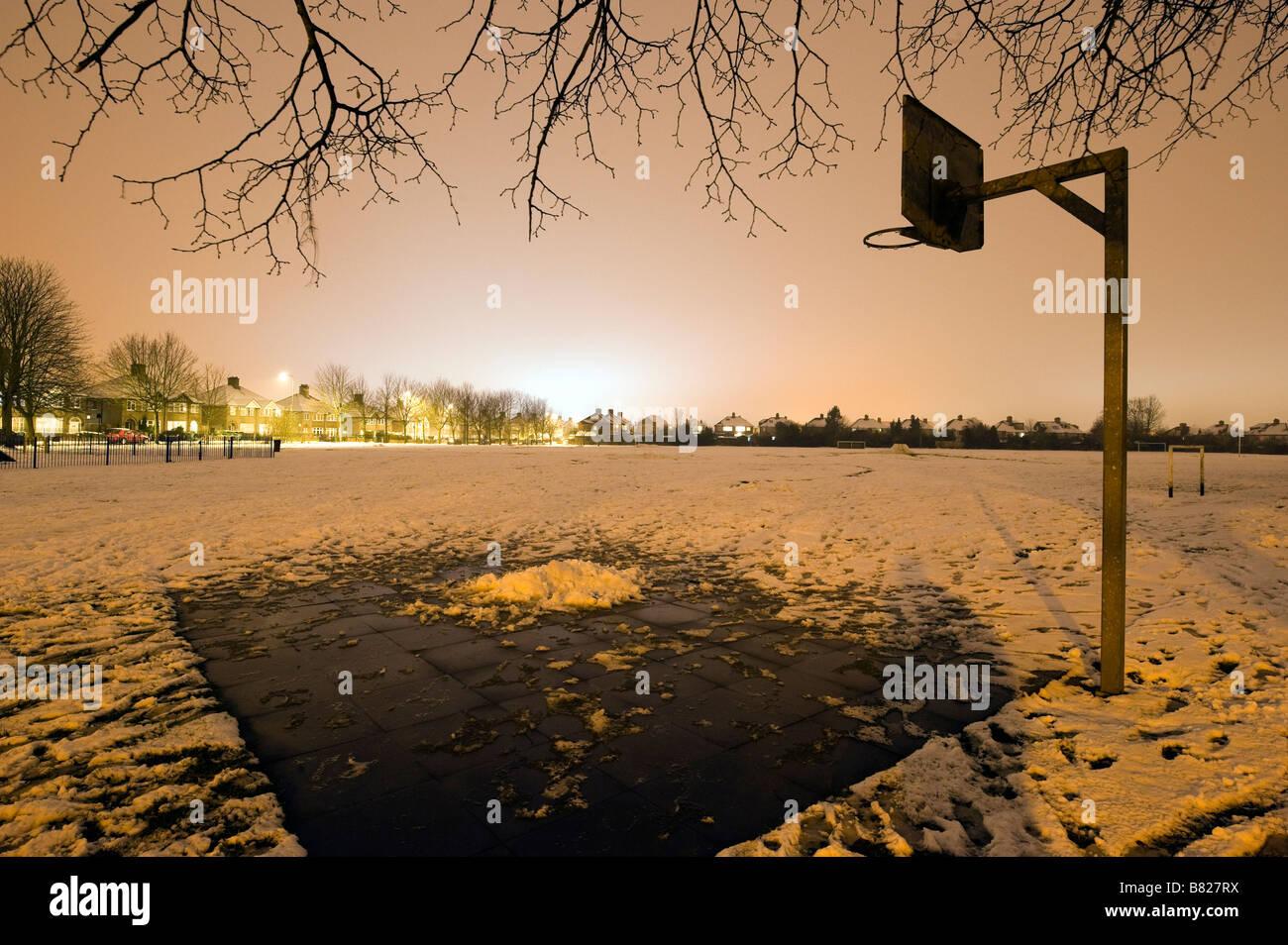 Basketball hoop su una coperta di neve al parco giochi per bambini di notte Immagini Stock