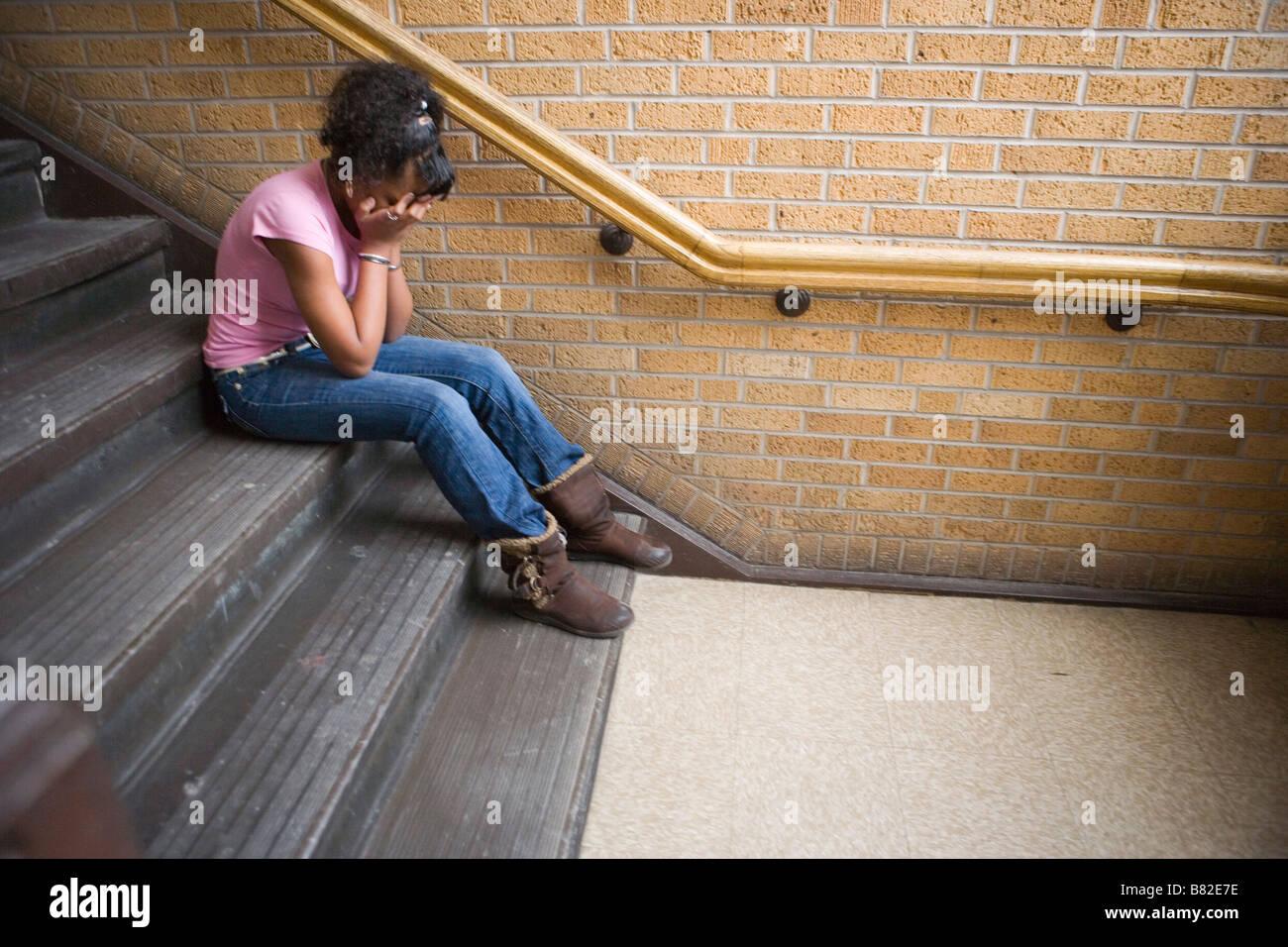 Adolescente americano africano ragazza piange sulla scalinata a scuola, udienza del passo Immagini Stock
