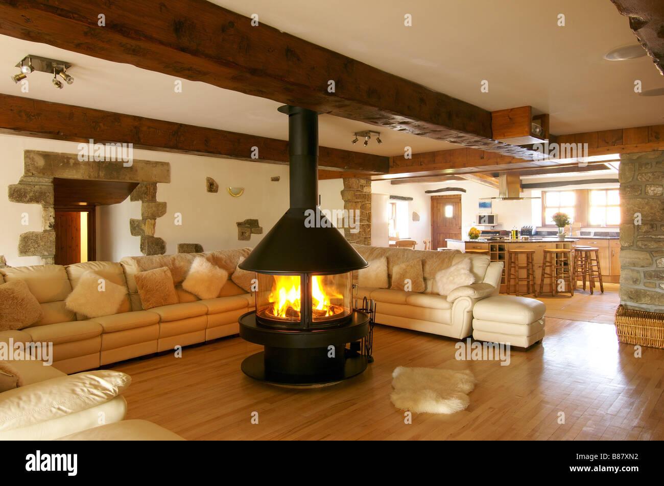 Soggiorno con un grande divano ad angolo e caminetto centrale con ...