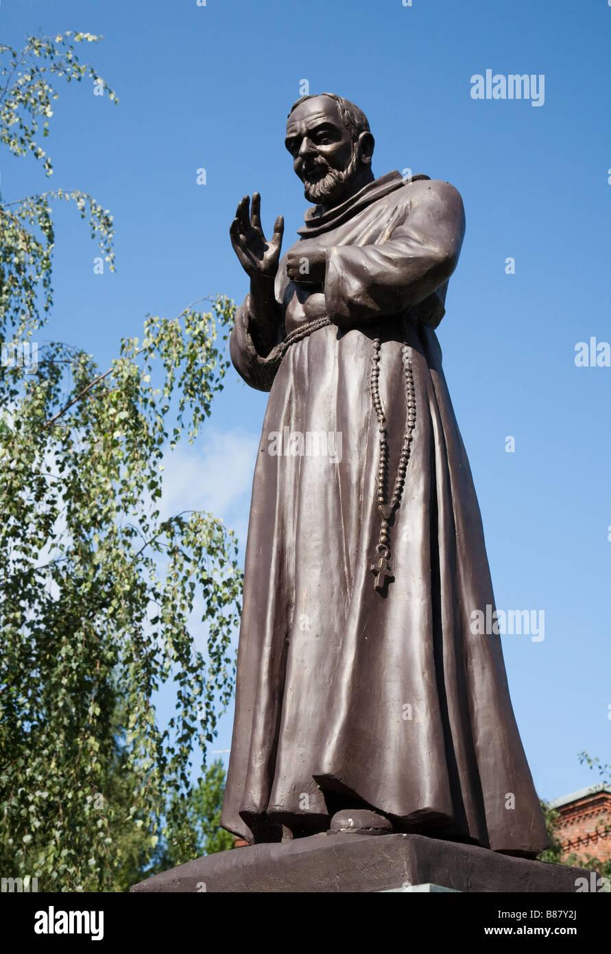 La statua di Pio da Pietrelcina aka Padre Pio con la Chiesa Cattolica Romana di San Otto dietro Slupsk Polonia Immagini Stock