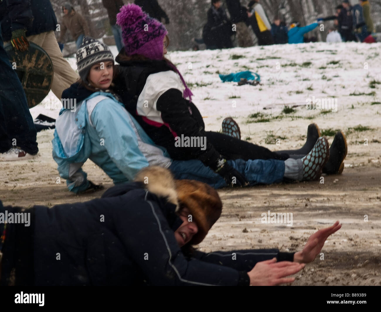 La donna tira un volto di uomo cade lo slittino Immagini Stock