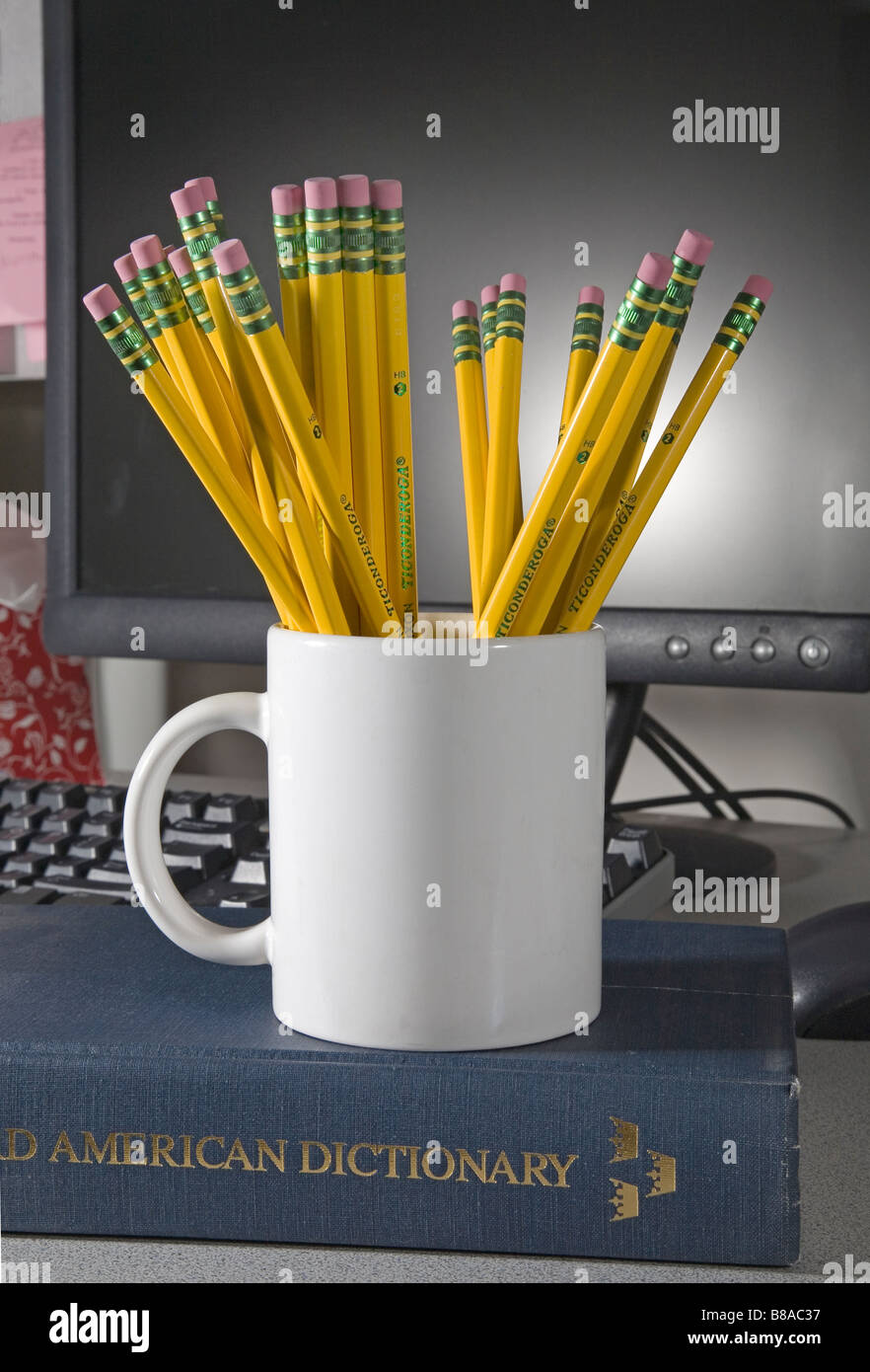 Una tazza o tazza alta di numero 2 Ticonderoga piombo o matite di grafite e cancellatori di fronte a un computer Immagini Stock