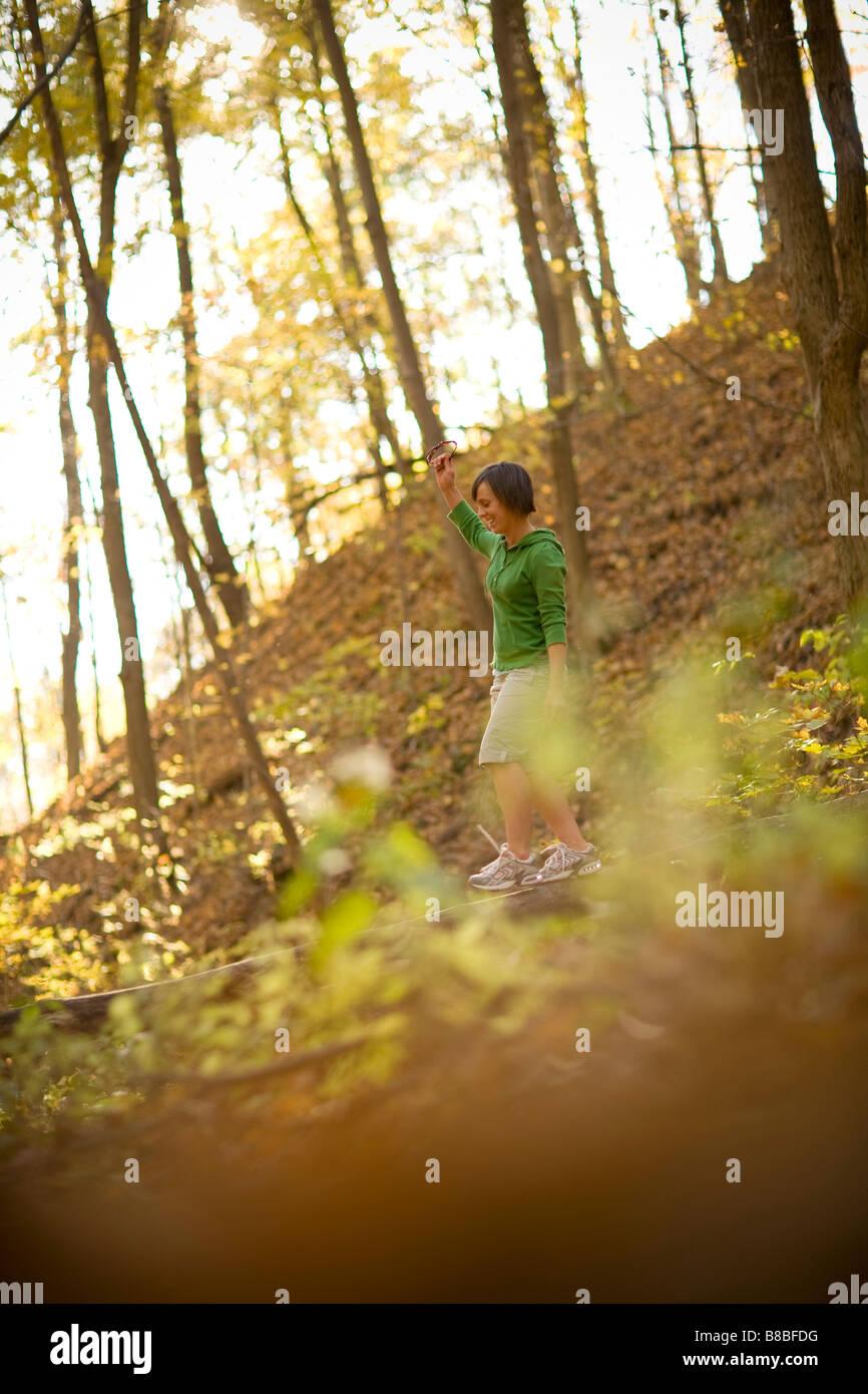 Donna in equilibrio su caduto albero tronco nel bosco Immagini Stock