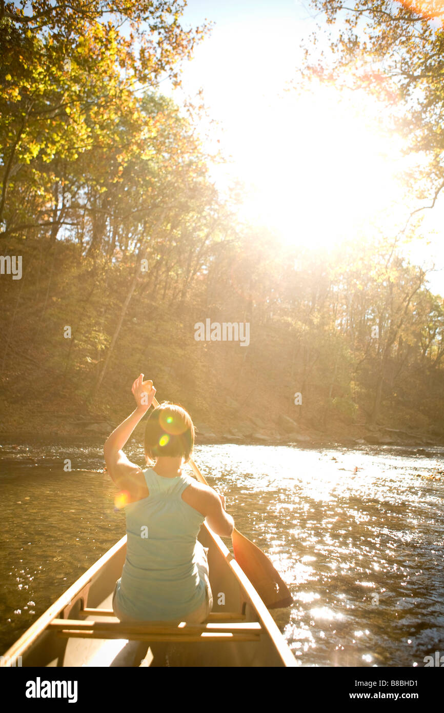 Donna discese in canoa lungo il fiume Immagini Stock