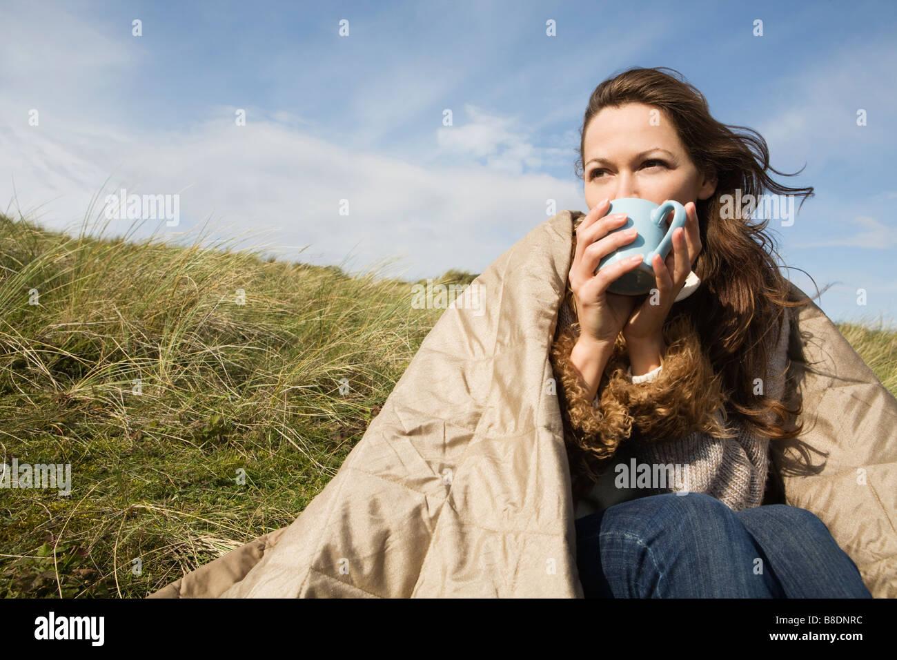 Donna all'aperto con coperta e bere Immagini Stock