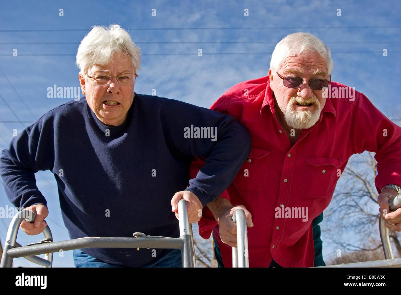 Coppia di anziani si prepara a corsa utilizzando i camminatori, concorrenza umorismo, scherzando Foto Stock