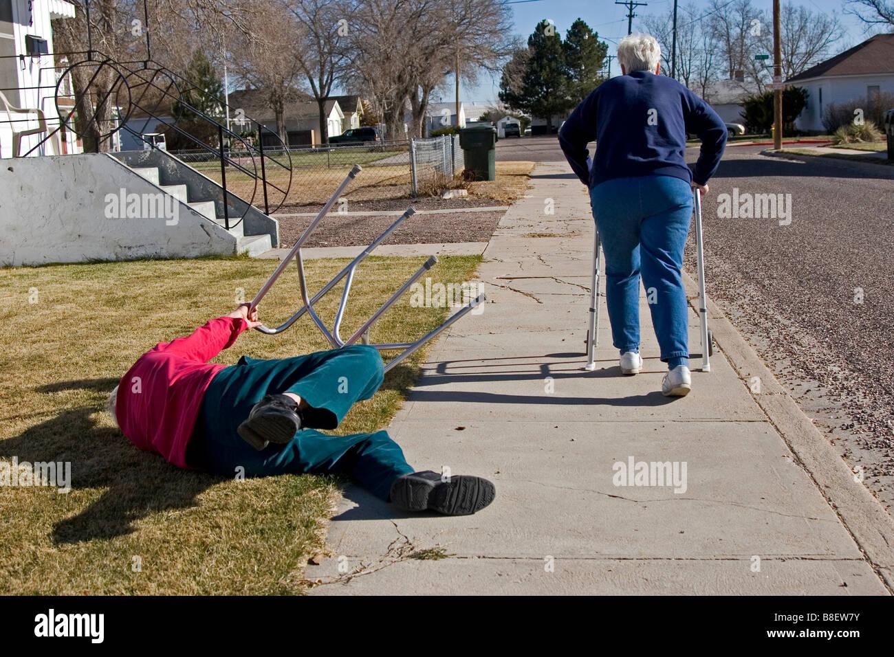 Due anziani anziani a piedi utilizzando i camminatori, la donna è scattato l'uomo che è caduto giù, divertente, 1 di 4 in serie Foto Stock
