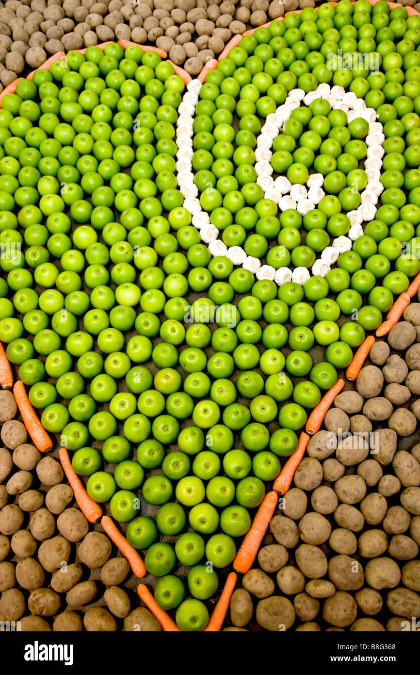 A forma di cuore ad arte fatta da frutta e verdura Immagini Stock