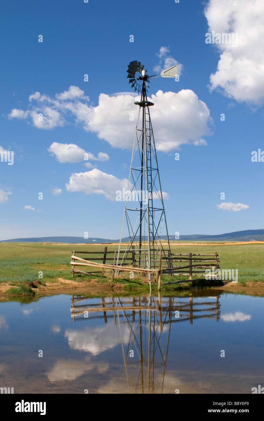 La riflessione di un mulino a vento industriale in acqua, Wyoming USA Immagini Stock