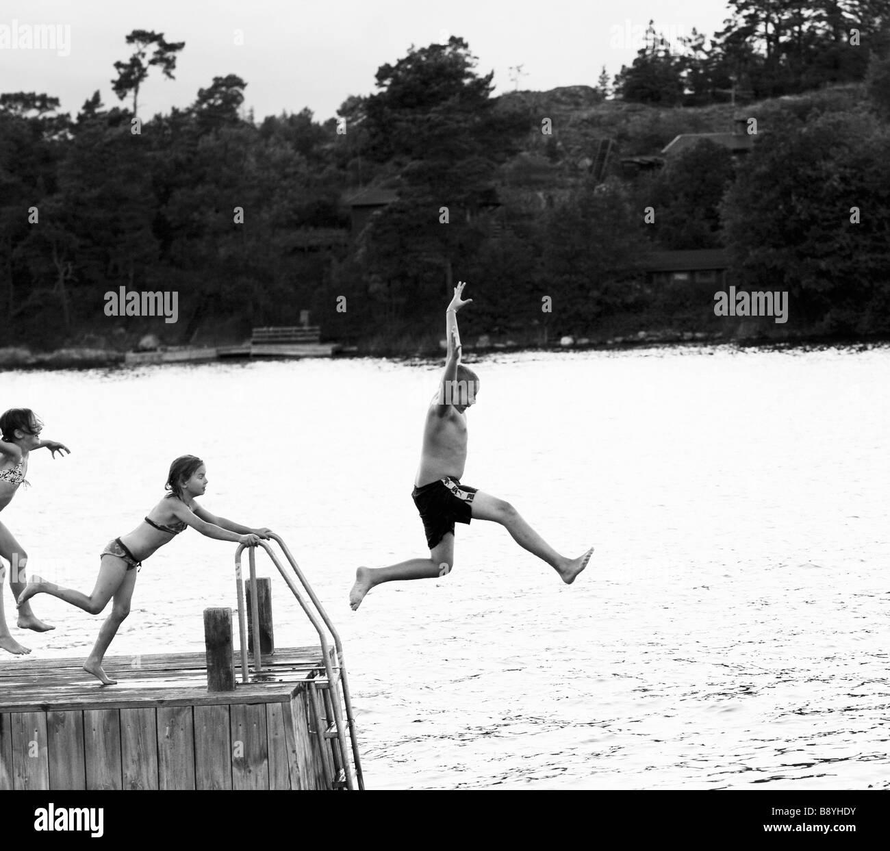 Tre bambini che salta da un pontile della Svezia. Foto Stock