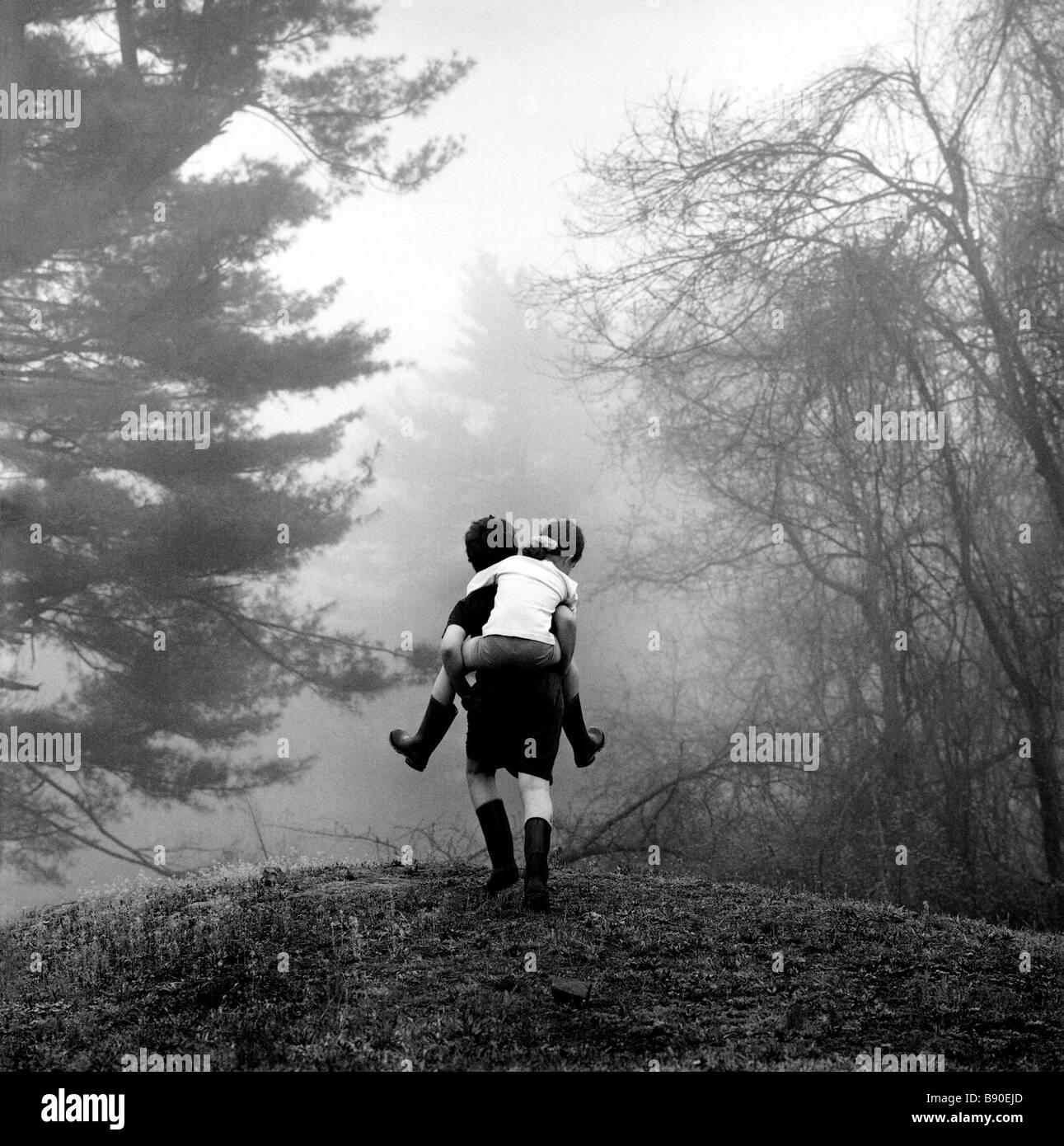 FL2608, NICK KELSH; Boy piggybacking ragazza attraverso boschi Immagini Stock