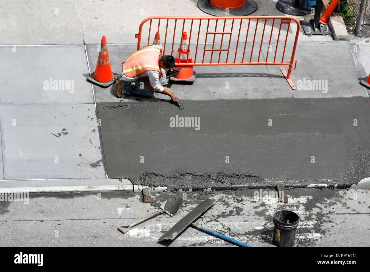 L'uomo una levigatura appena spillata calcestruzzo bagnato il marciapiede. Foto Stock
