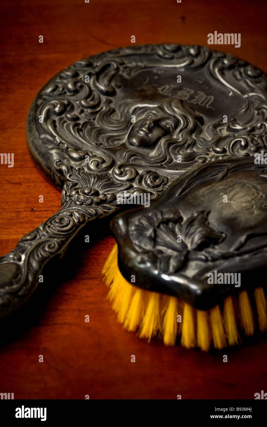 Ancora la vita di un antico pennello e specchio a mano con un disegno decorativo di una donna con lunghe ciocche Immagini Stock