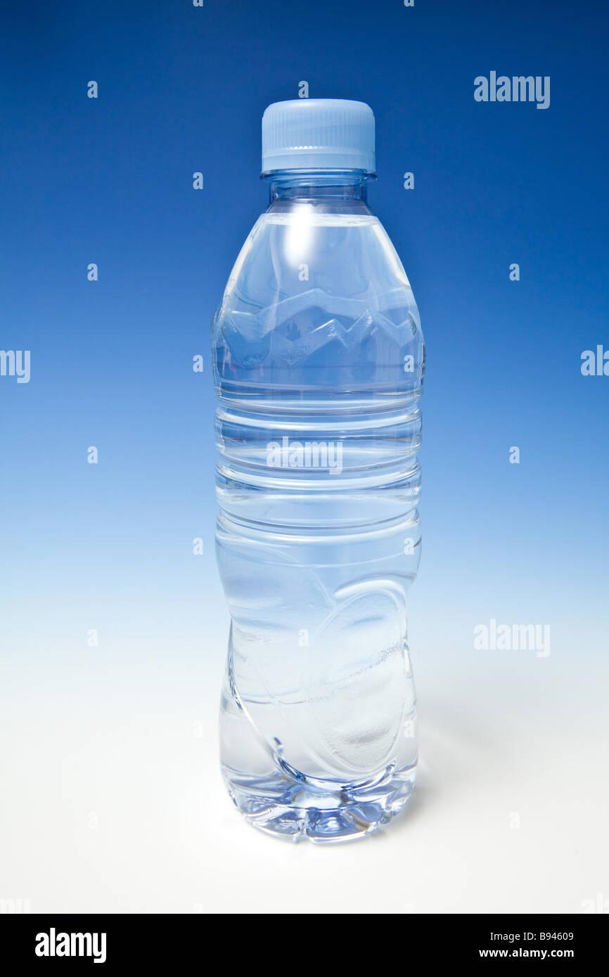 Acqua in bottiglia su una graduazione blu di sfondo per studio Immagini Stock