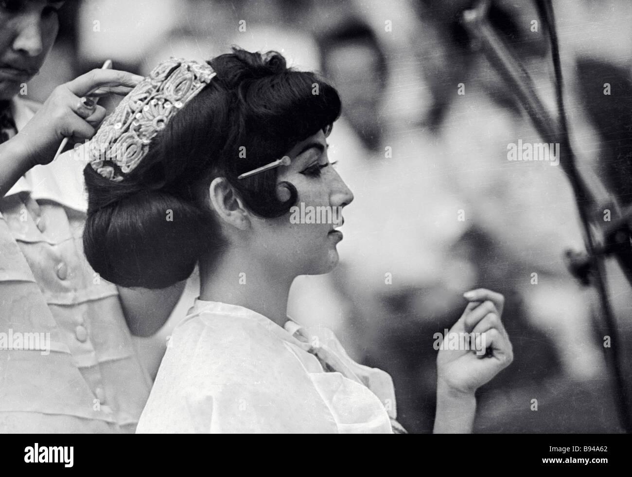 Una ragazza tagika indossando una calotta adornata con fili dorati Immagini Stock