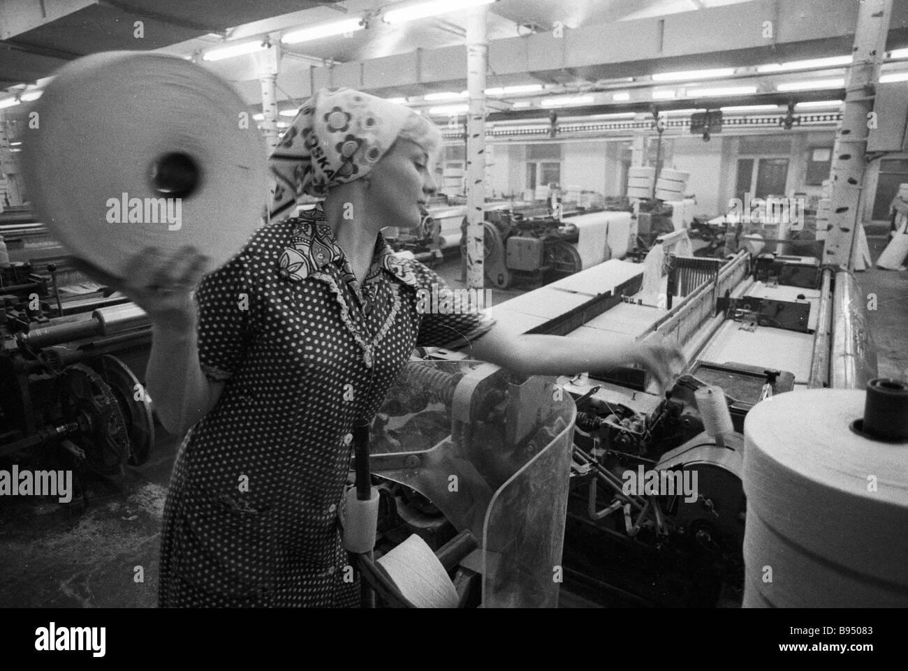 Un impianto tessile operaio il funzionamento di un telaio di tessitura Immagini Stock
