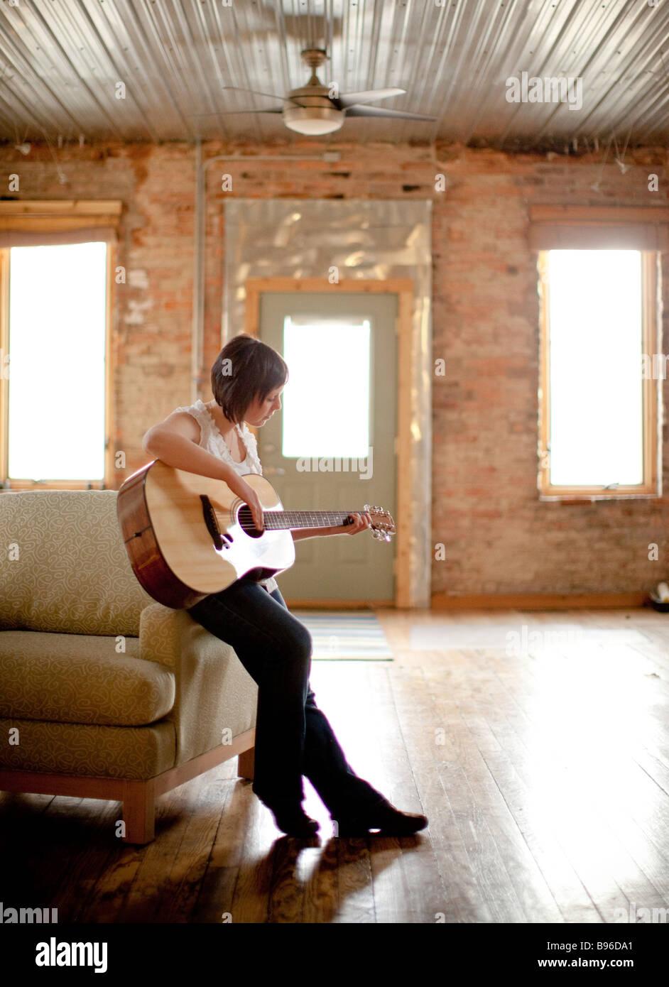 Giovane donna a suonare la chitarra in spazi urbani Immagini Stock
