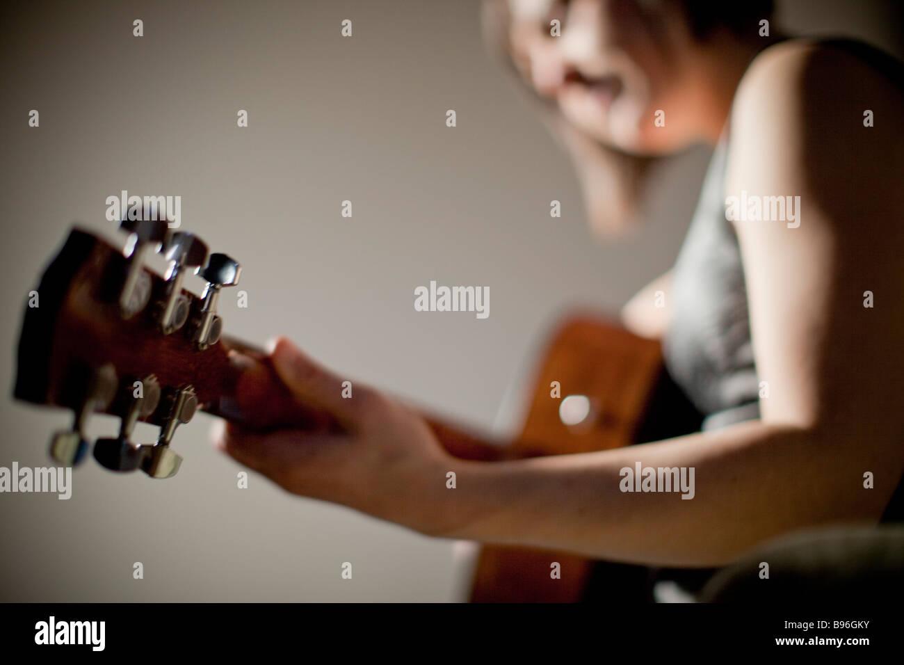 Giovane donna a suonare la chitarra Immagini Stock