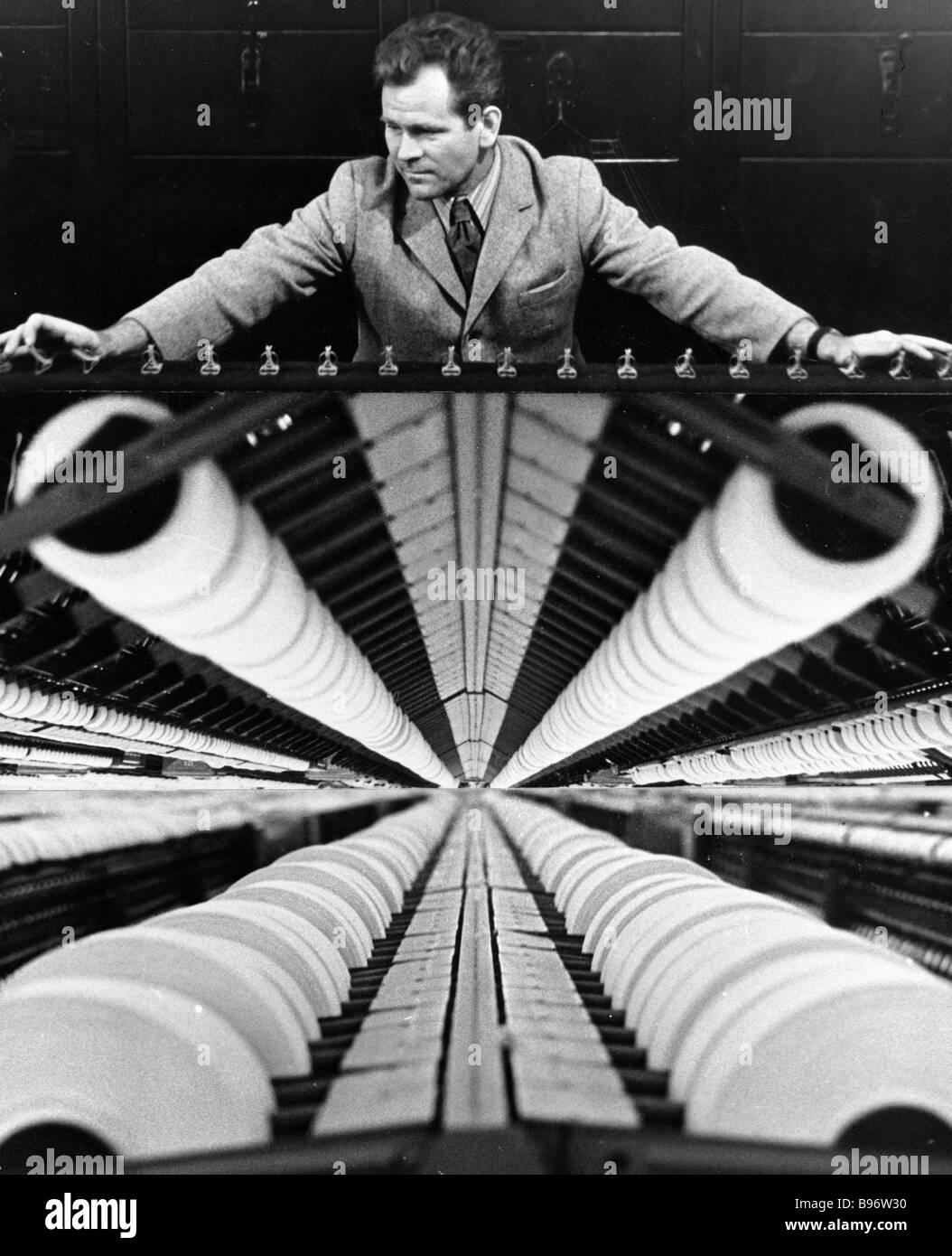 Un lavoratore in un impianto tessile Immagini Stock