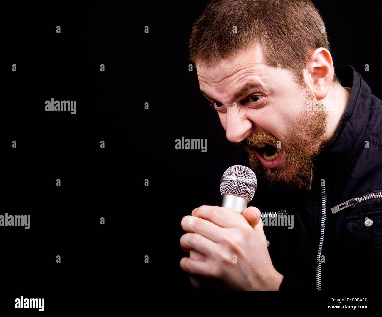 Urlo del maschio a bilanciere arrabbiato al microfono con copyspace Immagini Stock