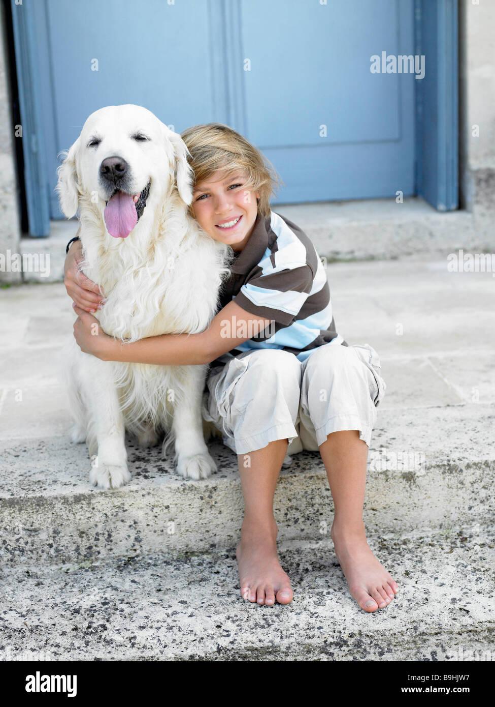 Ragazzo con cane sul gradino della porta Immagini Stock
