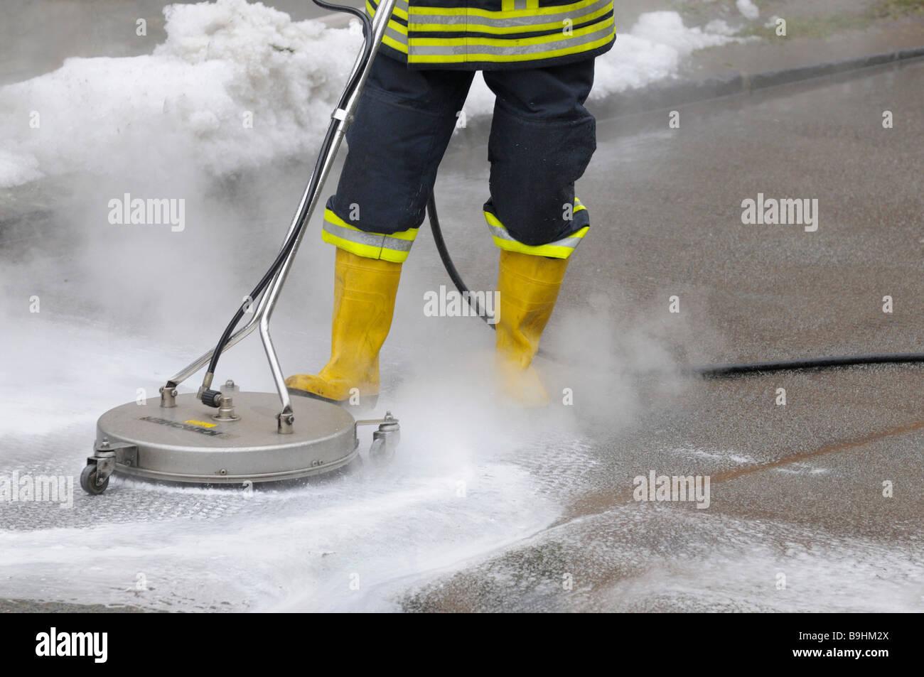 Fireman trapelare neutralizzante liquido dei freni da una strada con apparecchiature per la pulizia Immagini Stock
