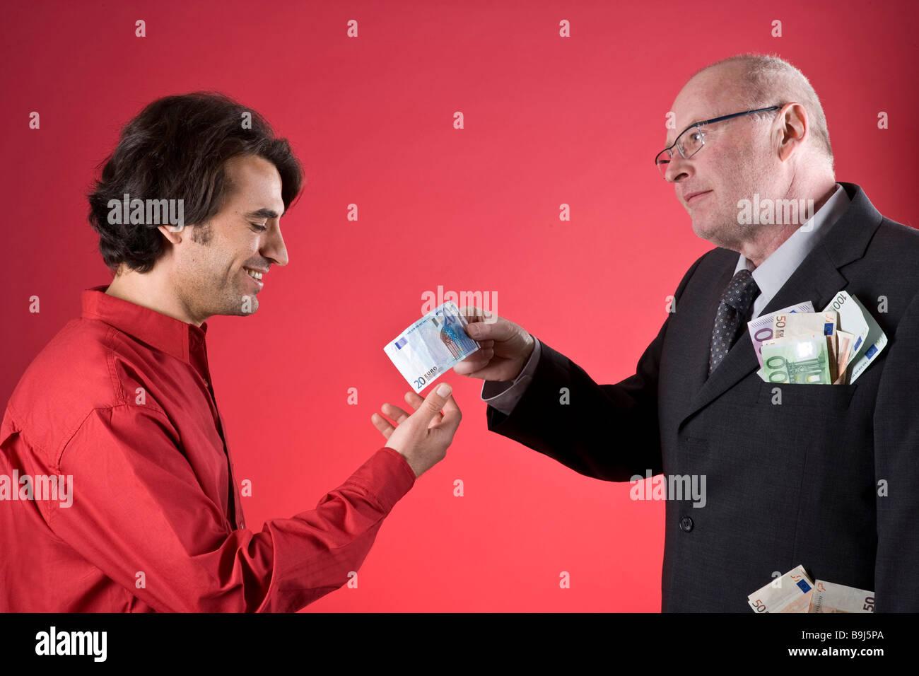Ricco imprenditore con tasche completa offrendo giovane uomo denaro Foto Stock
