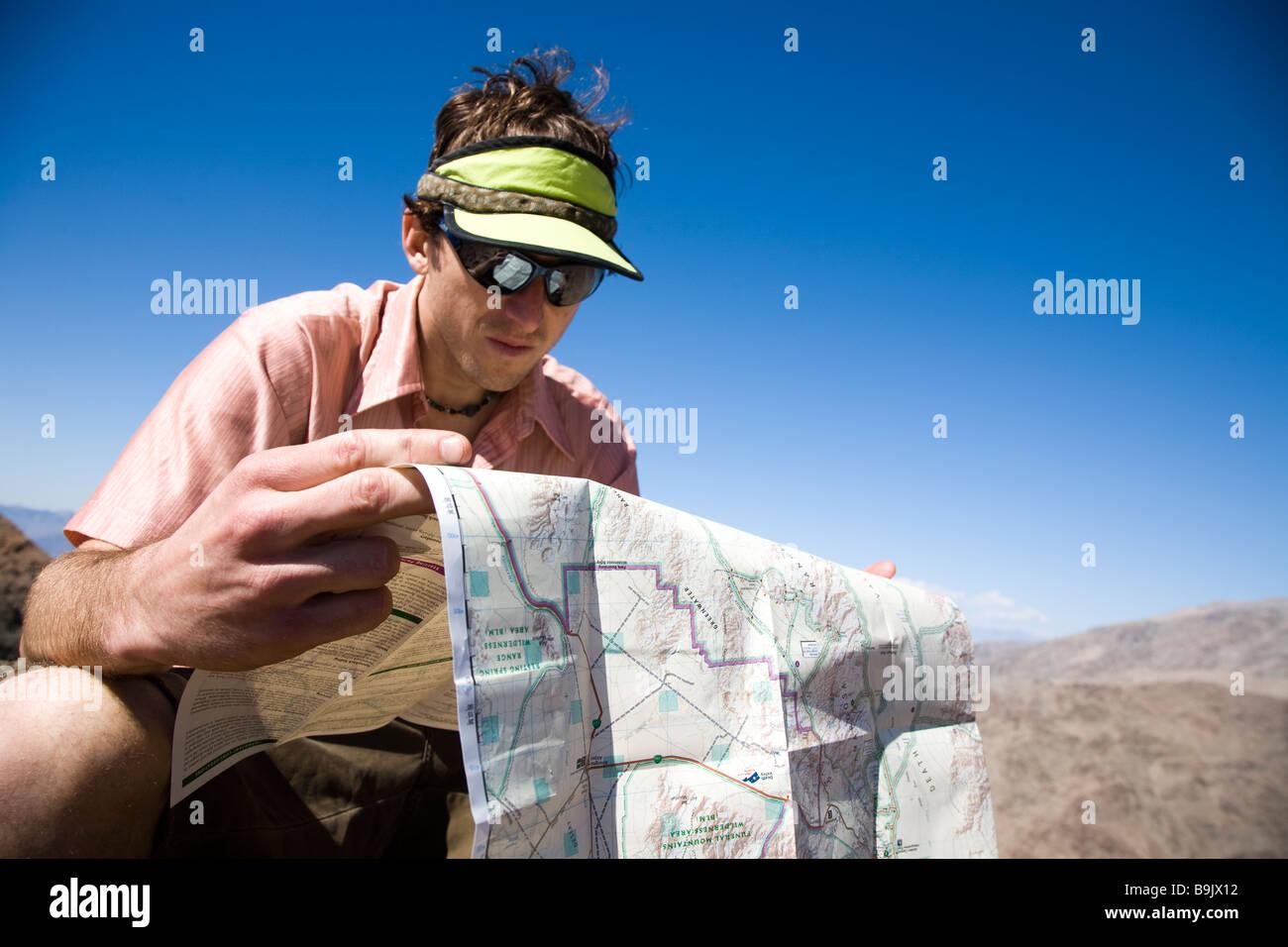 Un escursionista guarda una mappa alla sommità di un picco nel Parco Nazionale della Valle della Morte, California. Immagini Stock