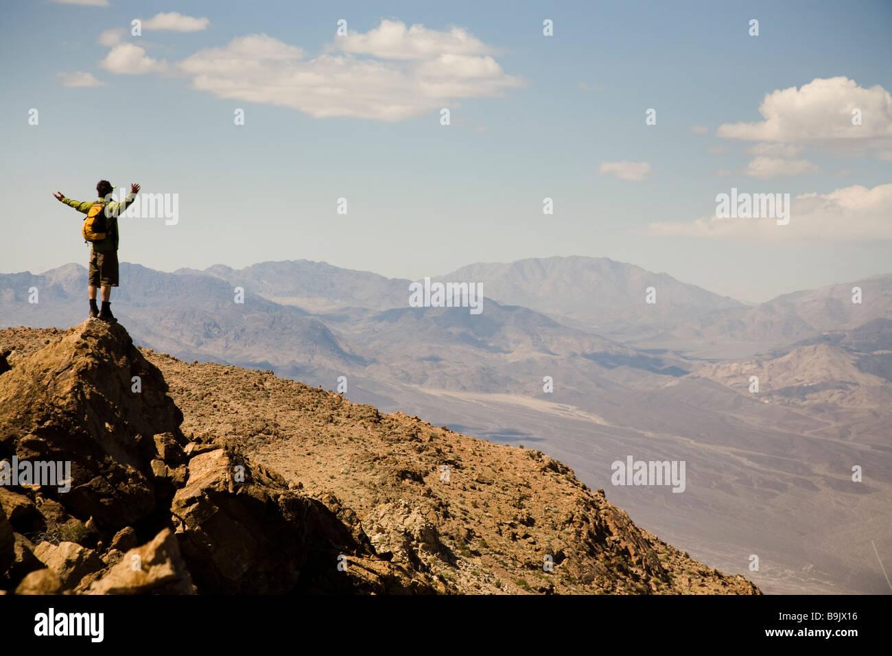 Un uomo sta con le braccia estese al vertice di un picco nel Parco Nazionale della Valle della Morte, California. Immagini Stock