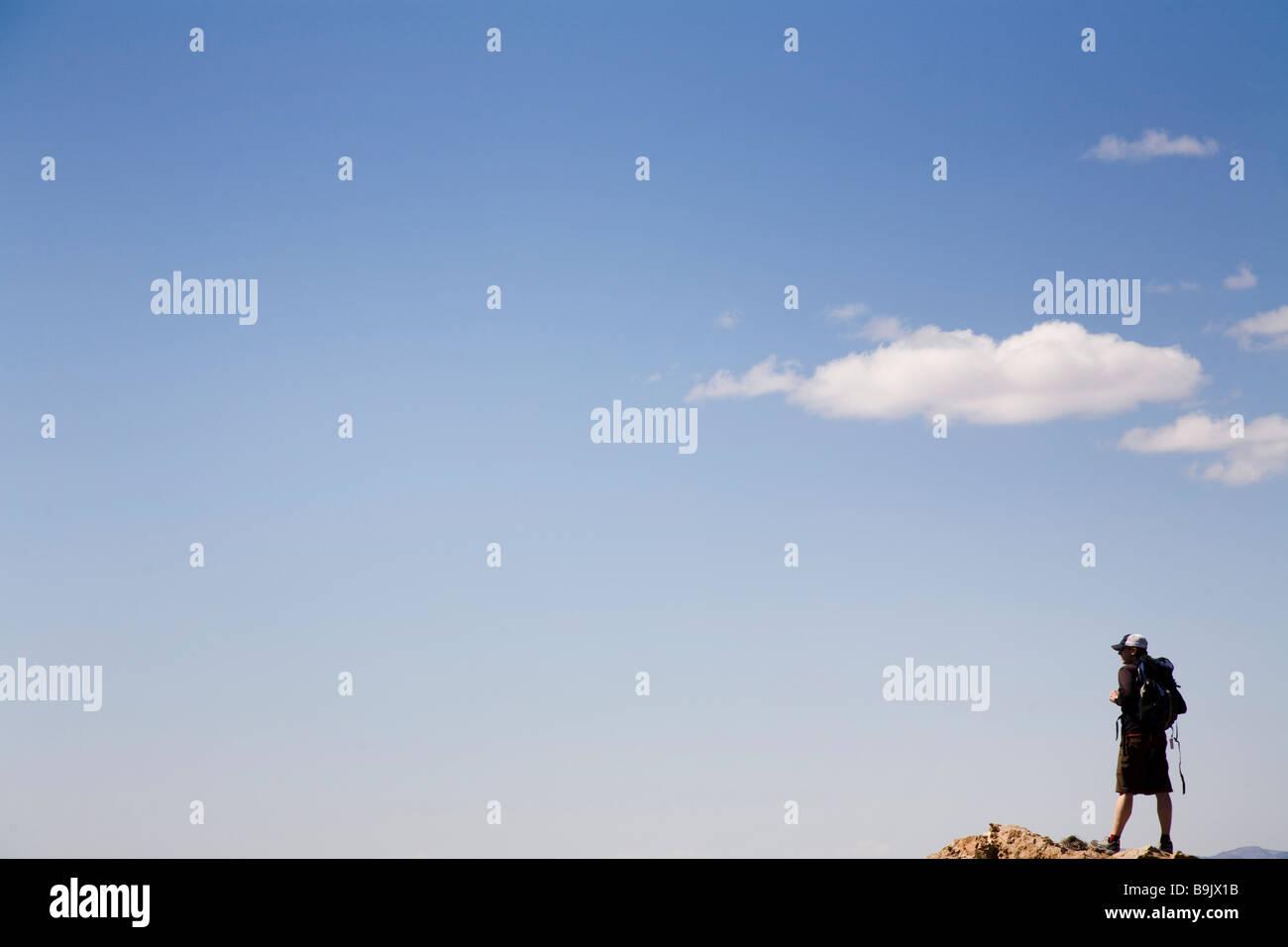 Un uomo si erge su un si affacciano con solo il cielo blu dietro di lui nel Parco Nazionale della Valle della Morte, Immagini Stock