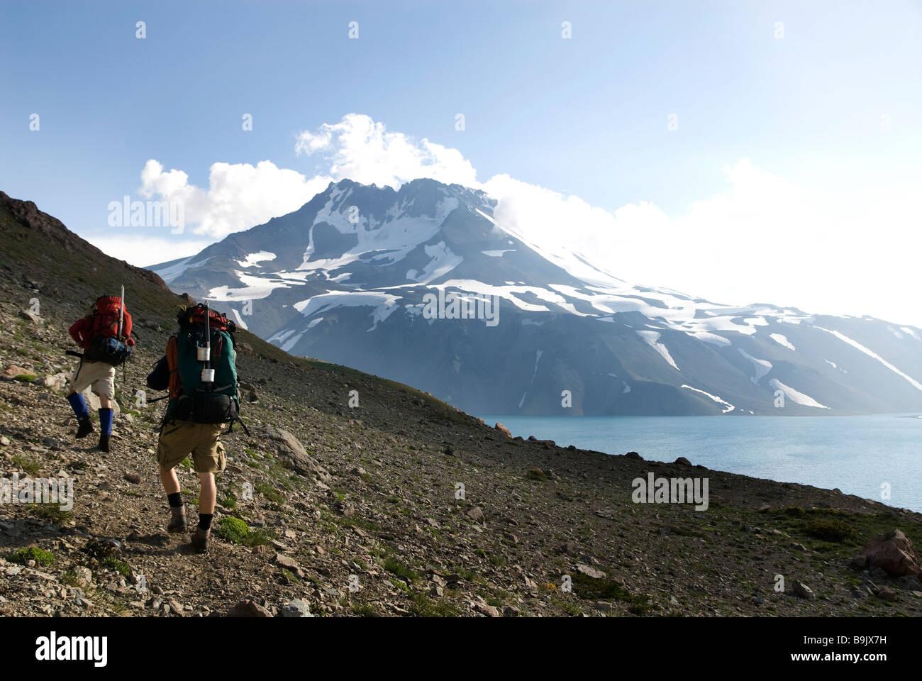 Due backpackers seguire un sentiero intorno a un lago alpino vicino al confine di Cile e Argentina. Immagini Stock