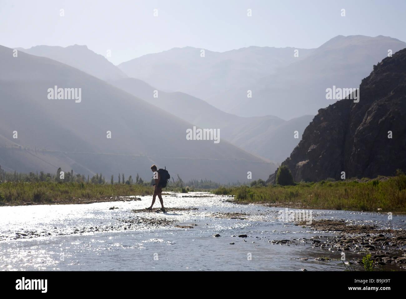 Un giovane uomo, indossando uno zaino, attraversa un fiume poco profondo con grandi montagne sullo sfondo. Immagini Stock