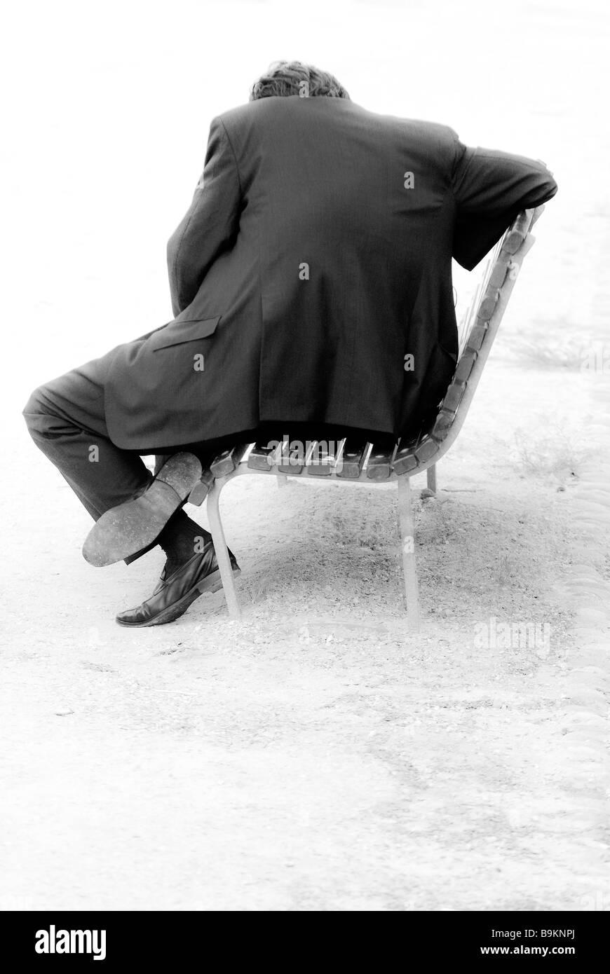 Uomo seduto su un banco di lavoro Immagini Stock