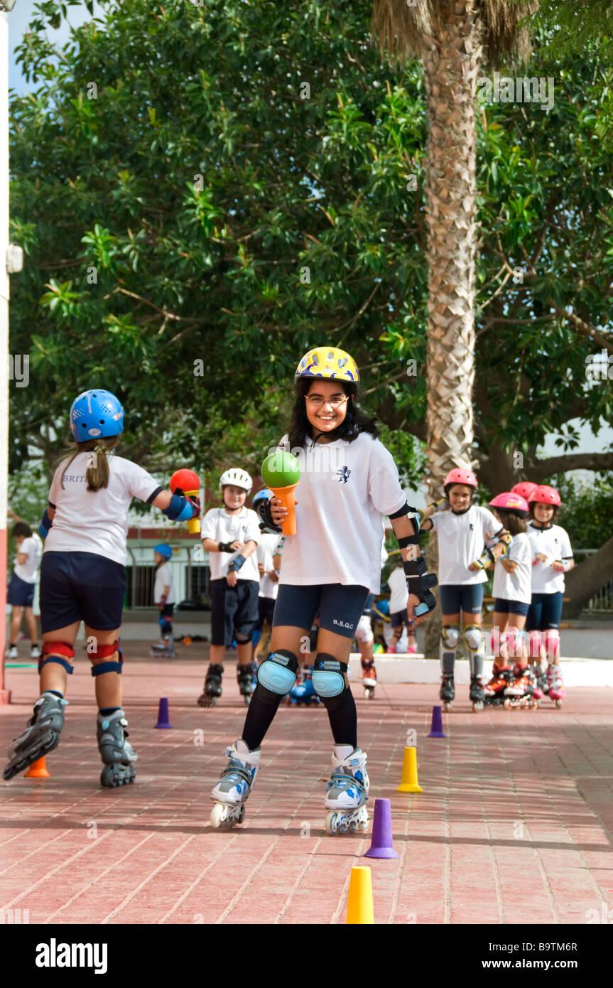 Squadre di junior scuola gli alunni competere in slalom rollerblade corso con la palla e la tazza di concorrenza Immagini Stock