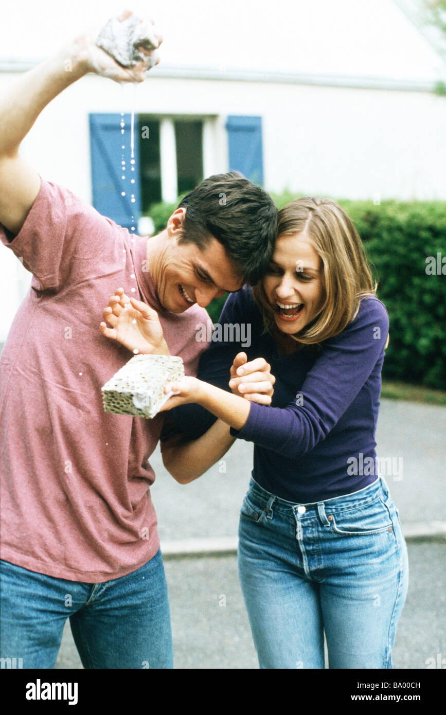Uomo spugna di spremitura, donna ridendo, cattura l'acqua con spugna Immagini Stock