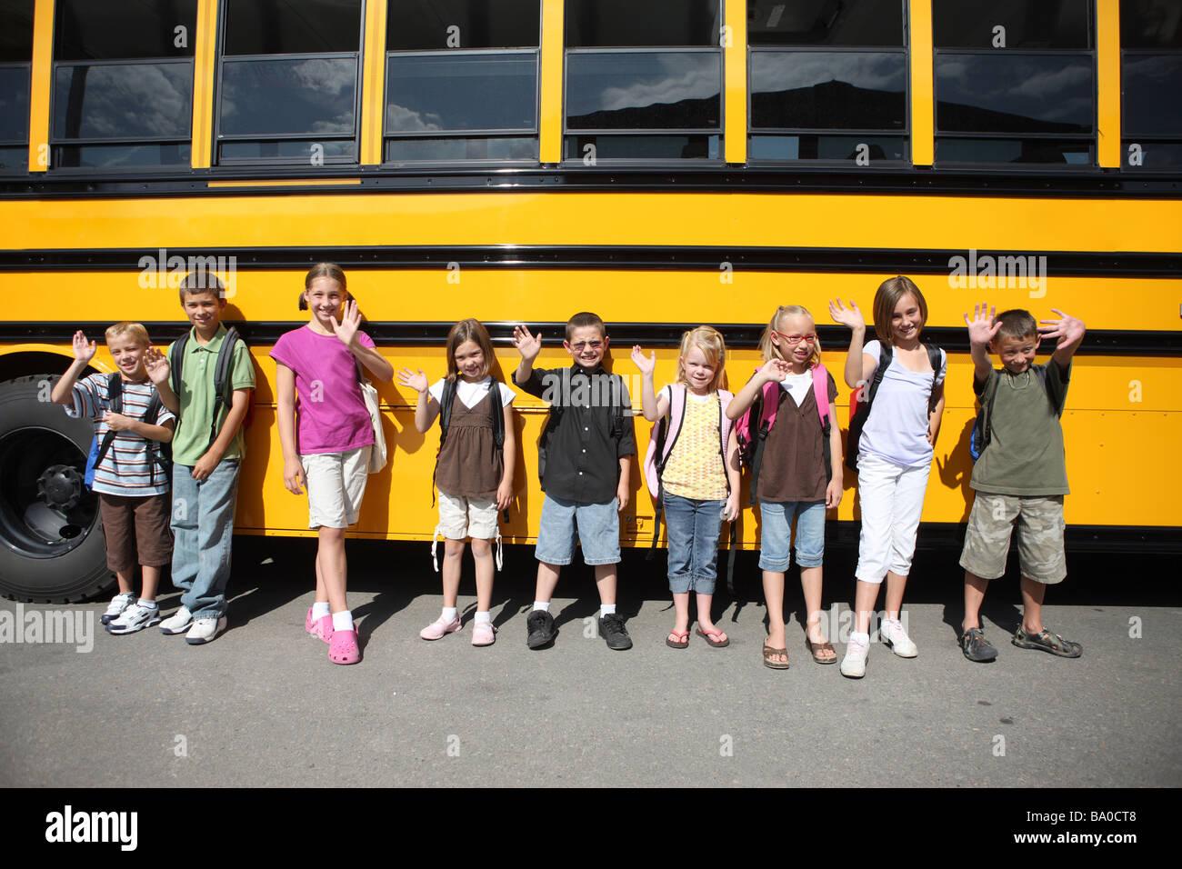 Gruppo di scolari nella parte anteriore del bus di scuola Immagini Stock