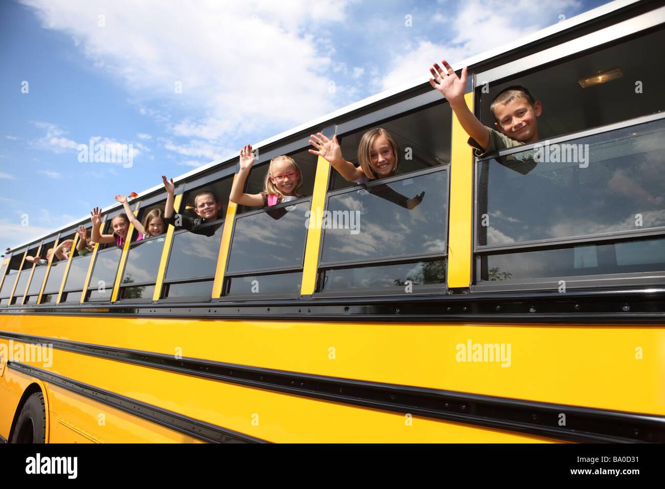 Bambini sventolando dal bus di scuola di windows Immagini Stock