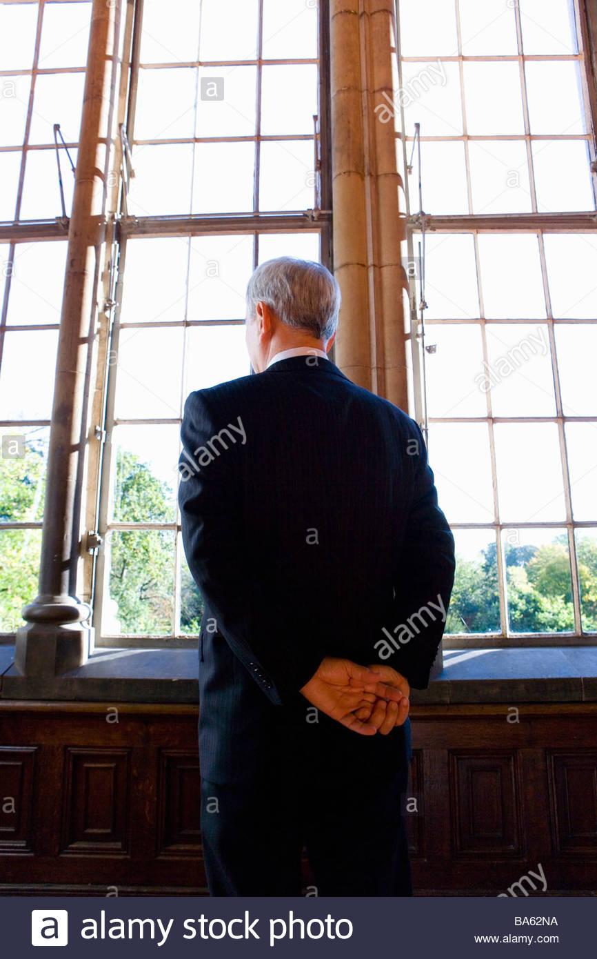 Imprenditore con braccia dietro la schiena, a guardare fuori dalla finestra, vista posteriore Immagini Stock