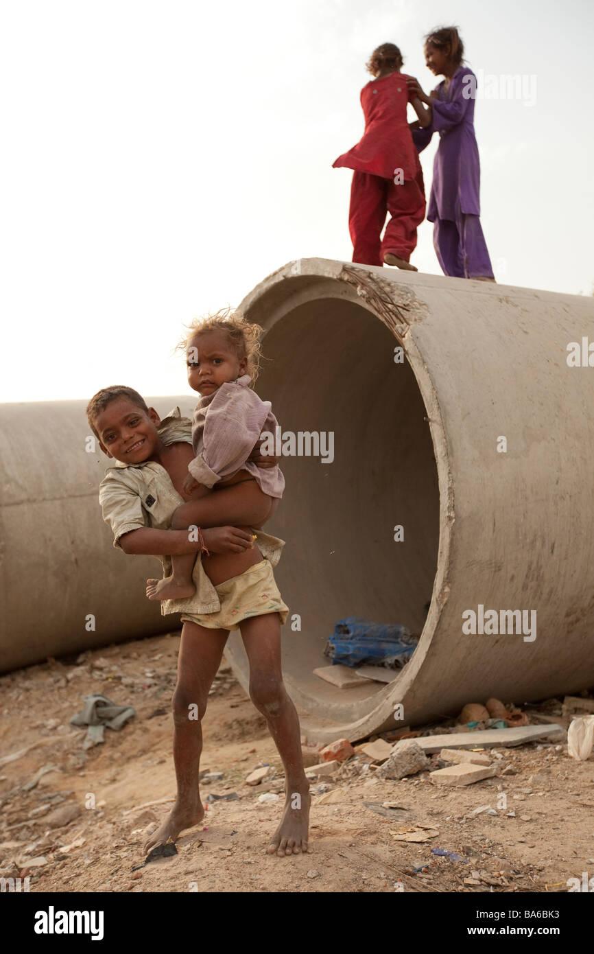 Un ragazzo indiano gioca con le sue sorelle tra tubazioni fognature Costruzione opposta zona in Gurgaon una città Immagini Stock