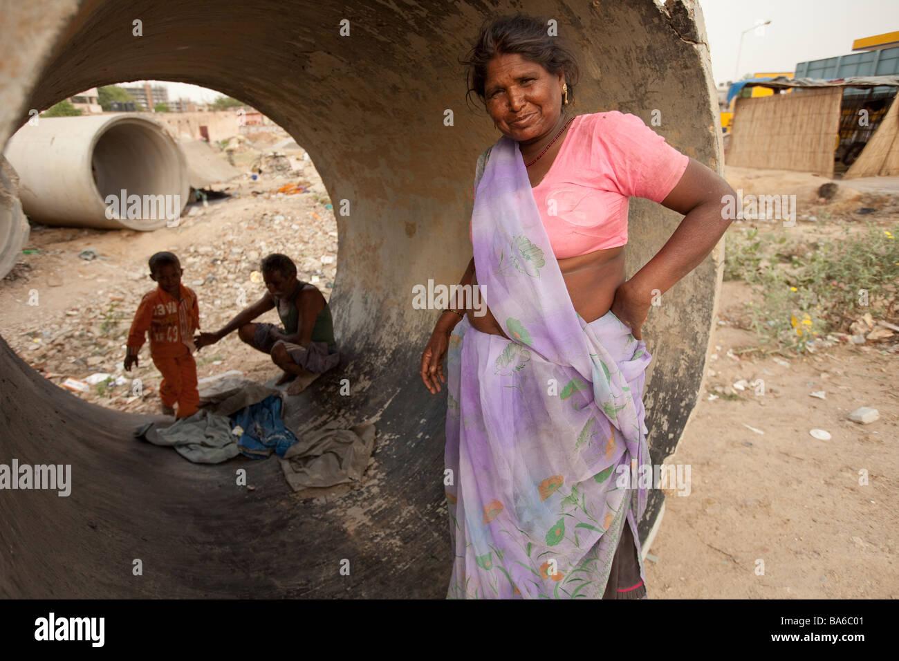 Una famiglia indiana accovacciata tra tubazioni fognature Costruzione opposta zona in Gurgaon una città satellite Immagini Stock